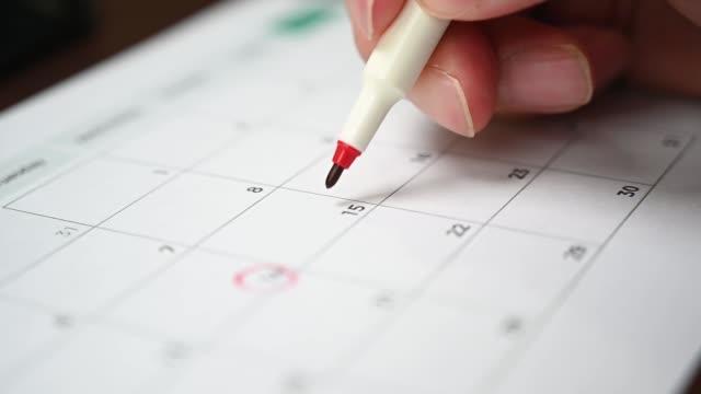 vídeos y material grabado en eventos de stock de cámara lenta. la mano de un hombre sosteniendo un bolígrafo en la mano y la grabación de su horario en un calendario de escritorio - calendar