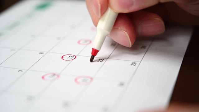 slow motion. The hand of a man holding a pen in his hand and recording his schedule on a desk calendar