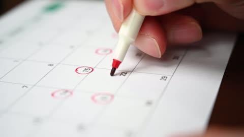 zwolnionym. ręka mężczyzny trzymającego długopis w ręku i nagrywającego jego harmonogram w kalendarzu biurkowym - data filmów i materiałów b-roll