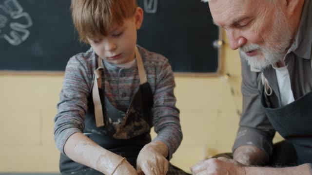 vídeos de stock, filmes e b-roll de câmera lenta inclinação de menino fazendo panela de argila usando roda de arremesso sob orientação de adulto - cerâmica artesanato