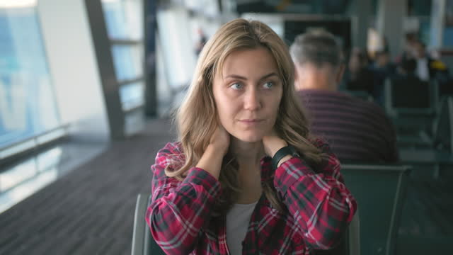 vídeos de stock e filmes b-roll de slow motion. tired young beautiful girl in red checkered shirt, is taken by the neck, sitting in the departure area of the international airport terminal. the concept of fatigue diseases of the spine, back, neck, head, osteochondrosis - criança perdida