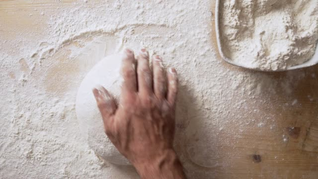 Slow motion top view of man's hands sprinkling flour over pizza dough and massaging it to prepare it for leavening at home on a light wooden board with white flour Slow motion top view of man's hands sprinkling flour over pizza dough and massaging it to prepare it for leavening at home on a light wooden board with white flour dough stock videos & royalty-free footage