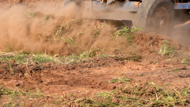 slow motion tractor plowing soil in farmland for planting and seeding season slow motion tractor plowing soil in farmland for planting and seeding season monoculture stock videos & royalty-free footage