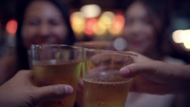 Slow motion - Traveler backpacker Asian women lesbian lgbt couple travel in Bangkok, Thailand. Female drinking alcohol or beer with friends and having party at The Khao San Road.