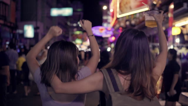 slow motion - traveler backpacker asian women lesbian lgbt couple dancing together. female drinking alcohol or beer with friends and having party at the khao san road in bangkok, thailand. - ночной рынок стоковые видео и кадры b-roll