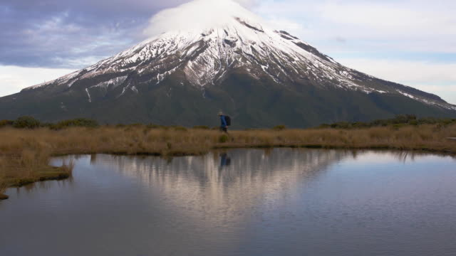 slow motion - traveler wlking cross view to the taranaki volcano in the north island of new zealand and with the reflection of tho mountain and the climber in a lake. new zeland - new plymouth filmów i materiałów b-roll