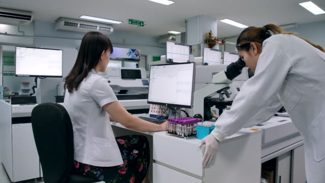 4k slow motion två forskare walking pratar om forskning rättegång sammanfattning i laboratoriet - medicinsk forskning bildbanksvideor och videomaterial från bakom kulisserna