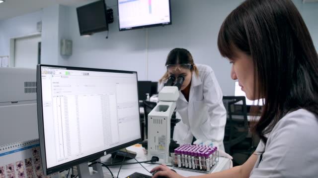 4kスローモーション 2人の科学者が研究室で研究試験の概要について話して歩いている - 研究所点の映像素材/bロール