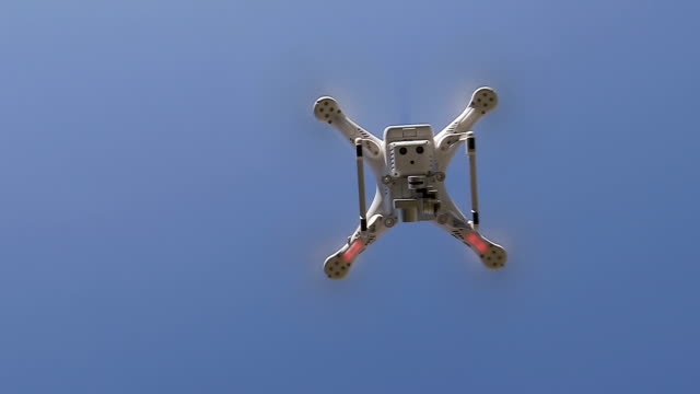 Slow motion underneath view of Drone rising vertitically into the sky video
