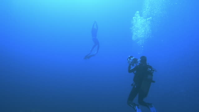 Slow motion underwater shot of a scuba diver being filmed swimming