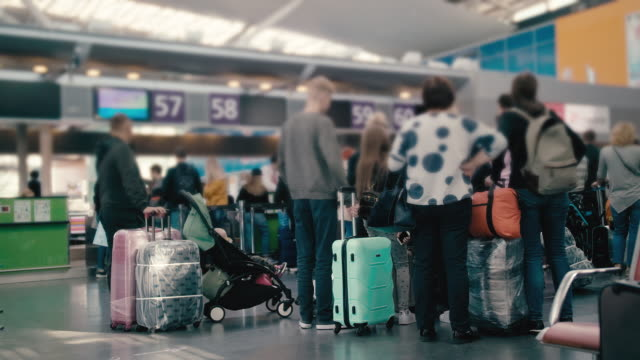 slow motion unrecognized family tourist grandmother with her teenage grandson, waiting in line for check-in at the international airport terminal. with suitcases of different colors - in fila video stock e b–roll
