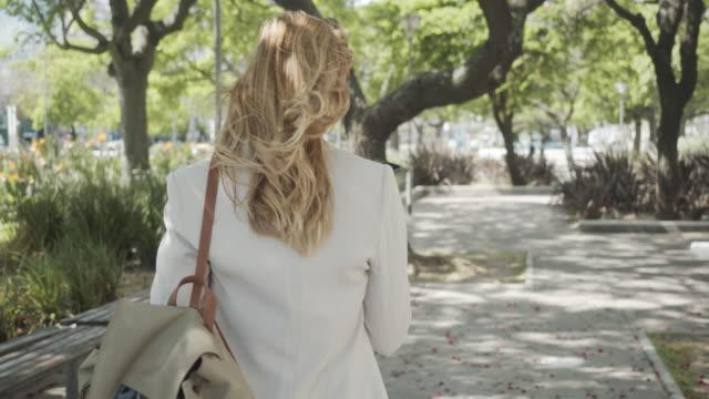 şehirde bir iş kadınının akıllı telefonla hoparlörden konuşurken verdiği yavaş çekim videosu - arka görüş - sarı saç stok videoları ve detay görüntü çekimi
