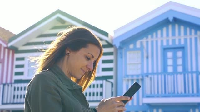 vídeos de stock e filmes b-roll de slow motion video of a caucasian woman using her phone on the beach at sunset - aveiro