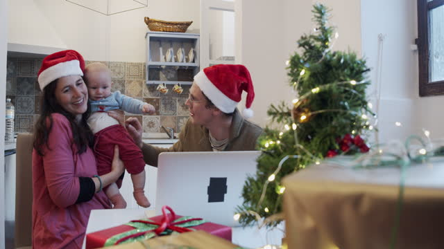 Slow motion video of a family celebrating Christmas, doing a video call with their relatives video