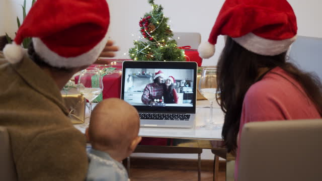 Slow motion video of a family celebrating Christmas with their relatives during a video call Slow motion video of a family celebrating Christmas with their relatives during a video call. The little kid is trying to open a gift. New normal during Coronavirus Covid-19 pandemic concept. holiday stock videos & royalty-free footage