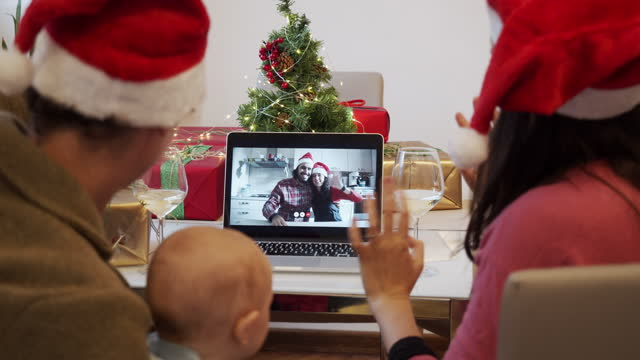 Slow motion video of a family celebrating Christmas with their relatives during a video call video