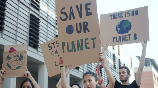 slow motion video of a group of people participating in a protest against global warming - clima video stock e b–roll