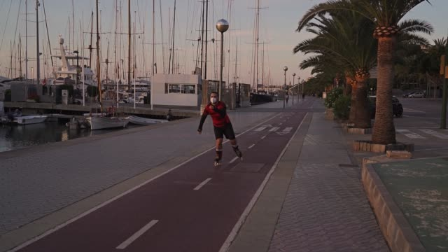 slow motion video of a new normal situation: a man in spain wearing a protection mask doing sport during the allowed times at a bike lane on palma de mallorca harbor on sunrise. he's with roller skate - new normal video stock e b–roll
