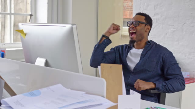 Slow motion video of a successful creative businessman celebrating good news at office video