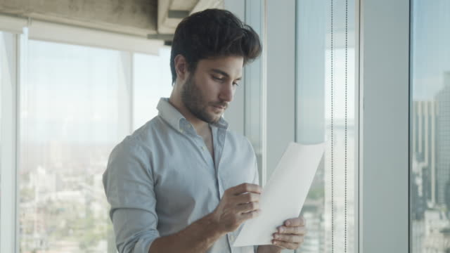 vídeos de stock e filmes b-roll de slow motion video of a young adult businessman in a modern office - carta documento