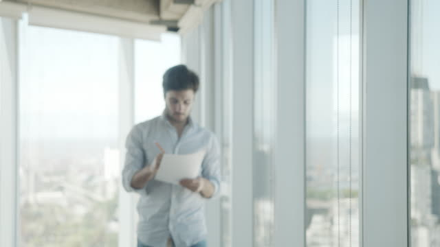 Slow motion video of a young adult businessman in a modern office video