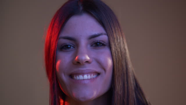 Slow motion video of a young adult woman opening eyes and smiling in front of the camera with colorful lights