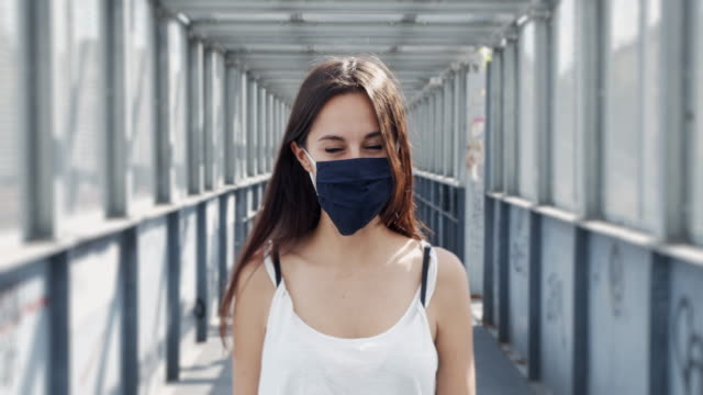 Slow motion video of a young adult woman while she's wearing a protective facemask video