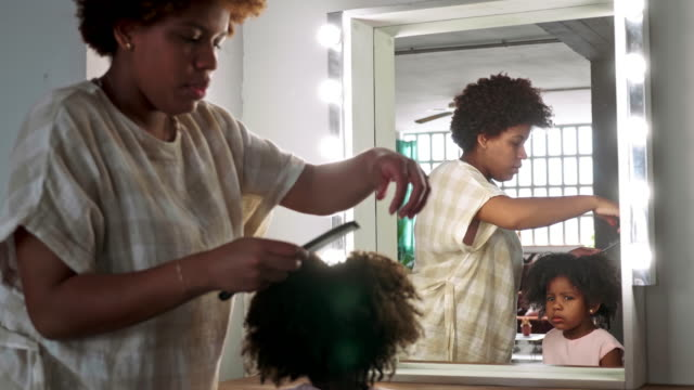 Slow Motion Video of Afro-Caribbean Mother Combing Hair of 3 Year Old Daughter