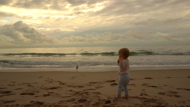 Slow motion video of baby girl plays with her doll on the beach