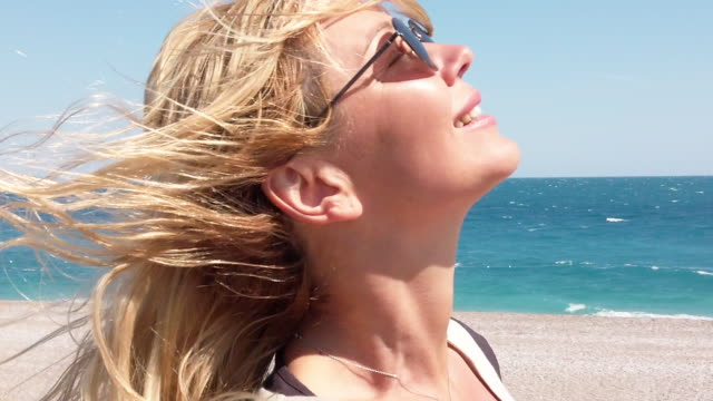 slow motion video of beautiful woman at the beach in a windy day - sorriso aperto video stock e b–roll