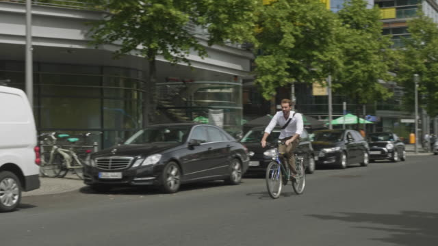 Slow motion video of businessman commuting by bicycle in the streets of Berlin Slow motion video of businessman commuting by bicycle in the streets of Berlin. mid adult men stock videos & royalty-free footage