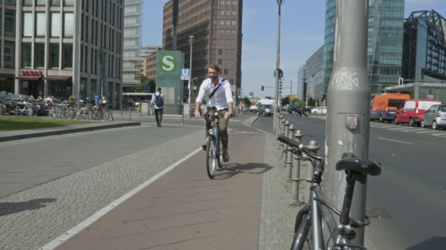 slow motion video of businessman commuting to work in the city by bicycle - pedone ruolo dell'uomo video stock e b–roll