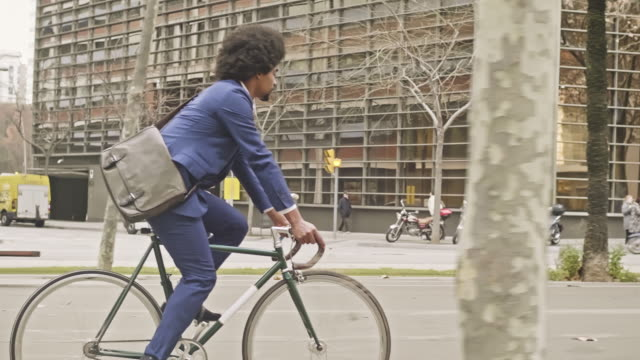 slow motion video of businessman commuting with his bicycle in the city - baffo peluria del viso video stock e b–roll