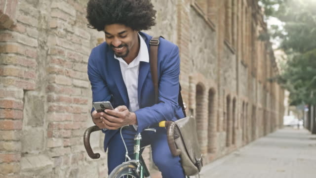 slow motion video of businessman leaning on his bicycle while texting a message with his mobile phone - veicolo a due ruote video stock e b–roll