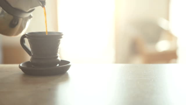 vídeos de stock, filmes e b-roll de vídeo de câmera lenta de mokka cafeteira derramando a donzela fresca em copo de barro preto pequeno na mesa close-up vista. preparação de café nas fitas cinematográficas de conceito de cozinha moderna. - comida feita em casa
