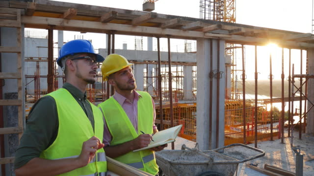 Slow motion video of construction industry - architects and engineers working together Construction industry concept - architects and engineers discussing work progress between concrete walls, scaffolds and cranes. construction equipment stock videos & royalty-free footage