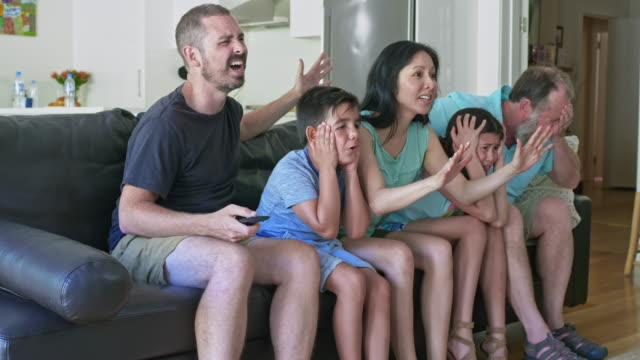 Slow motion video of family disappointed watching television Slow motion video of family disappointed watching a sport match on television. family watching tv stock videos & royalty-free footage