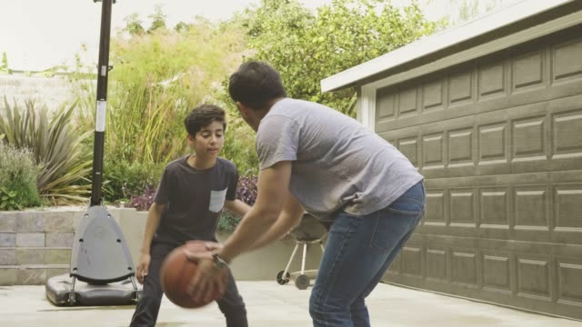 Slow motion video of father and son playing basketball at home Slow motion video of father and son playing basketball at home, father is scoring and after that they high-five. son stock videos & royalty-free footage