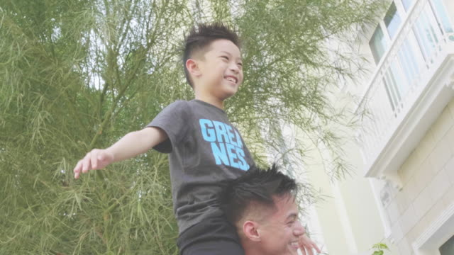 vídeos de stock e filmes b-roll de slow motion video of filipino father having fun with his son on his shoulder - etnia filipina