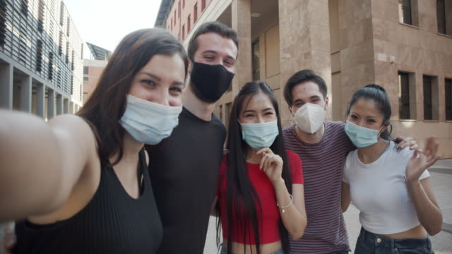 Slow motion video of five friends taking a selfie together, wearing facemasks video