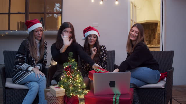 Slow motion video of friends celebrating Christmas together with other people during a video call video
