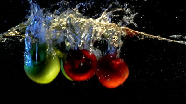 vídeos de stock, filmes e b-roll de vídeo de câmera lenta de maçã verde e vermelho, cair na água com bolhas. frutas em fundo preto isolado. - flutuando na água
