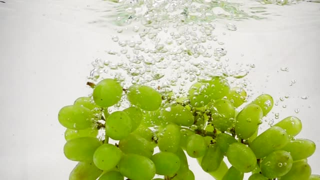 Slow motion video of green grapes. Bunch of grapes are immersed in water with bubbles.