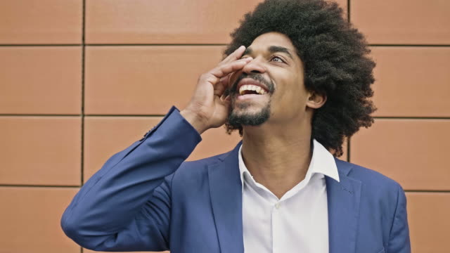 Slow motion video of happy Afro-Caribbean businessman smiling
