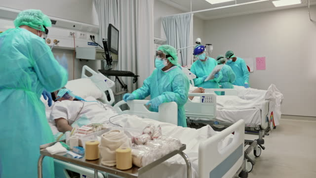 slow motion video of healthcare teamwork taking care of patients in icu - covid ospedale video stock e b–roll