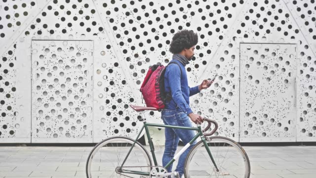 slow motion video of hipster with bicycle walking in the street with mobile phone - funky video stock e b–roll