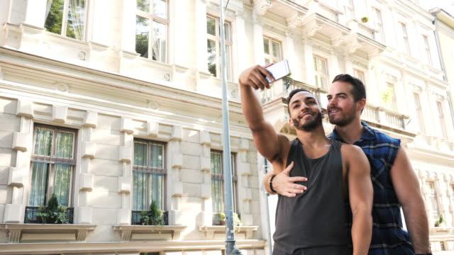vídeos de stock, filmes e b-roll de vídeo em câmara lenta de casal lgbt viajando no verão e tirando selfie - lgbt