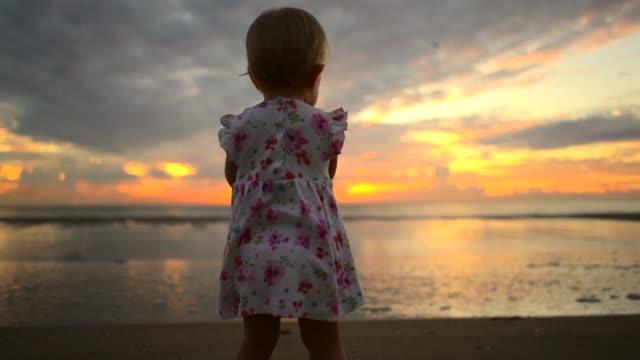 slow motion video of little child on the beach - nastro per capelli video stock e b–roll