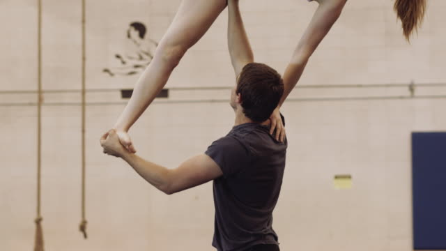 Slow motion video of male gymnast holding woman with one arm video