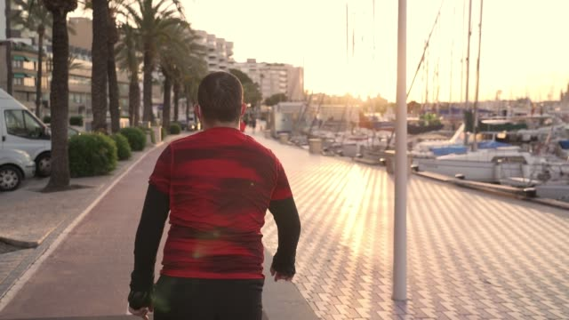 slow motion video of new normal situation: a man in spain wearing a protection mask doing sport during allowed times at a bike lane on palma de mallorca harbor on sunrise. there's also a flare on it - new normal video stock e b–roll